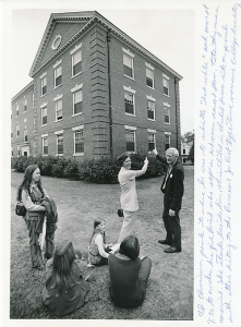 On a trip back to the old campus, Ed points to the Jean's dorm, where he used to whistle 'bob white' each morning. Daughter Kim sits on the sidewalk, enjoying this Romeo and Juliet story with WF students. About 1970. Photographer unknown.